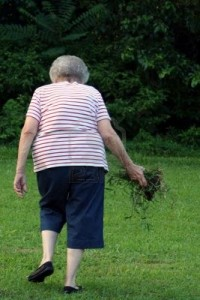senior-citizen-woman-cleaning-weeds-from-neighborhood-park-200x300
