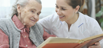 older woman with young female caregiver reading a book