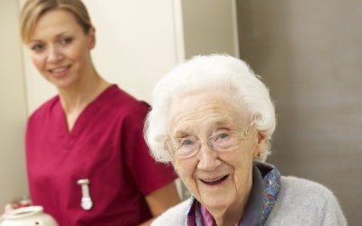 older woman walking with walker with a young female caregiver
